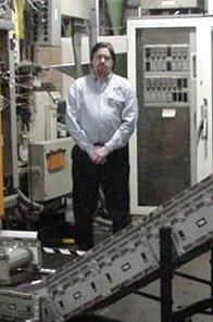 Mark Evjen standing in front of a DynaCon conveyor at Custom Bottle
